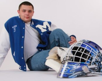 Guy posing in studio with his letterman jacket on & his hockey helmet for a senior picture
