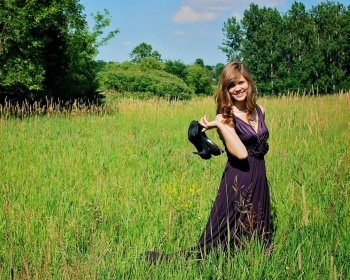 Girl posing in a field holding her shoes for a senior picture